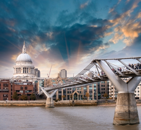 London, UK. Wonderful side view of Millennium Bridge at sunset, Saint Paul Cathedral on background.