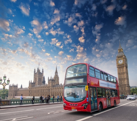 London. Classic red double decker bus crossing Westminster Bridge at sunset.