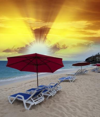 Desert beach with umbrellas and deckchairs at sunset. photo
