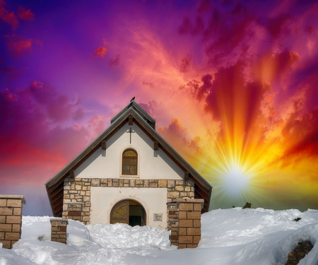 Chapel surrounded by snow on a mountan peak. Beautiful sunset colors in winter season. photo