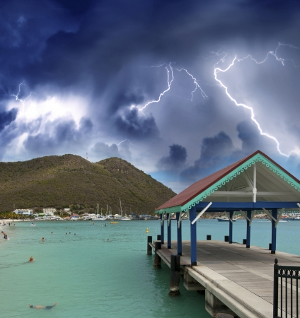 Thunderstorm over beautiful beach with jetty over water. photo