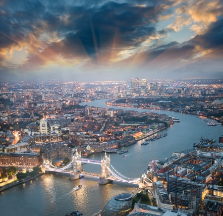 tilting: London. Aerial view of Tower Bridge at dusk with beautiful city skyline.