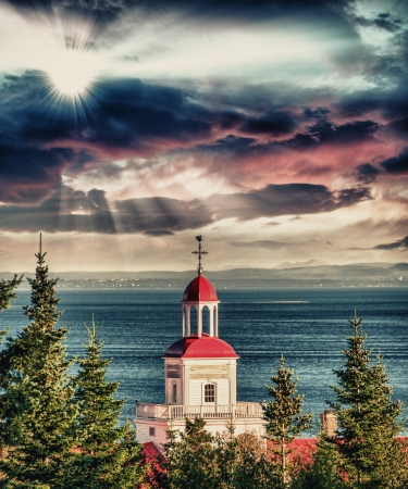 lawrence: Red buildings of Tadoussac, Quebec. Vegetation and Saint Lawrence river.