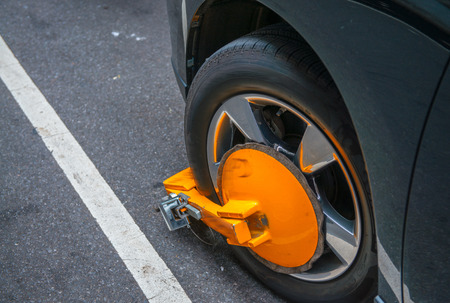 illegally: Yellow wheel clamp locked with messing lock on an illegally parked car.
