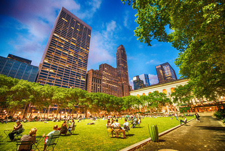bryant park: People relaxing on the grass of Bryant Park on a beautiful evening - New York.