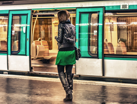 PARIS - NOV 28, 2012: Girl in front of a stopped train in the metro. The subway system carries more than 4 million passengers a day.