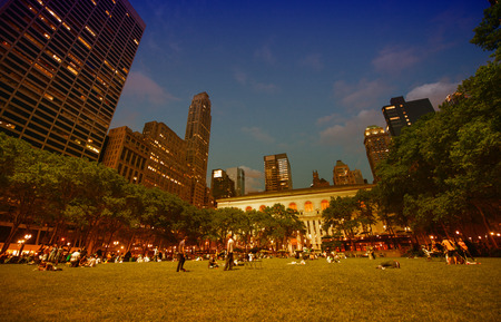 bryant park: NEW YORK CITY - JUN 8: Tourists relax at sunset in beautiful Bryant Park, June 8, 2013 in NYC. Bryant Park is a 9.603 acre (39,000 m²) privately managed public park. Editorial