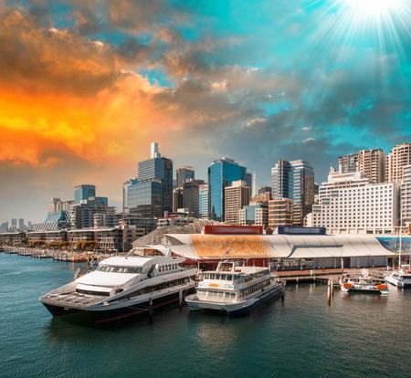 Sydney. Aquarium Ferry Wharf en de skyline van de stad in de schemering.