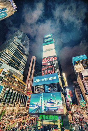 NEW YORK - JUN 12, 2013: Times Square ads and lights at night. Times Square is the brightly illuminated hub of the Broadway Theater District, one of the world's busiest pedestrian intersections Sajtókép