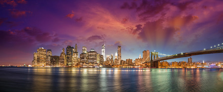 New York City Manhattan skyline panorama with Brooklyn Bridge and office skyscrapers buildings at dusk illuminated with lights at night. Stock Photo