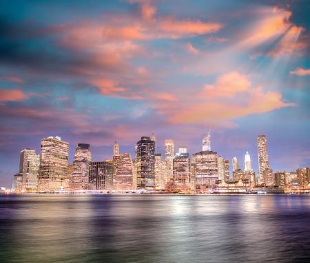 Stunning sunset in New York City. Lower Manhattan night skyline from Brooklyn Bridge Park.