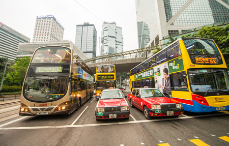 preferred: HONG KONG - APRIL 24, 2014: Red taxi cabs and colourful Buses, symbol of the city. Taxi cabs are very cheap in the city and one of the preferred transportation system.