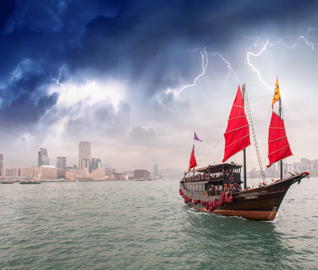 Sailing ship crossing the sea near a city during a storm. photo