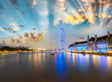 London skyline along Thames and famous London Eye wheel on a wonderful summer night.