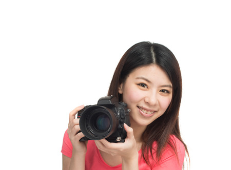 Pretty asian photographer girl happy shooting with her camera. Isolated on white. photo