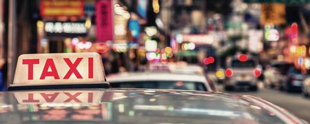 Taxi sign with Hong Kong city lights. Stock Photo