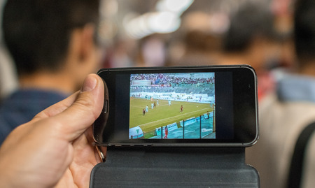 Watching a football match on mobile phone in the subway train photo