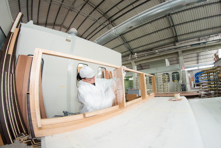 Manufacture process of carpenter work with wood at machining center during furniture manufacture.