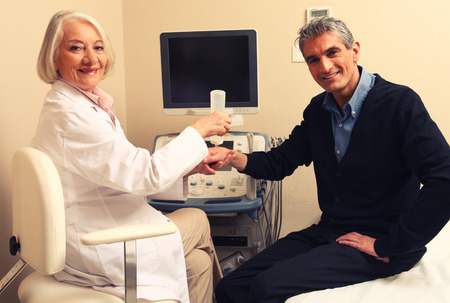 Mature female doctor examining man in 40s. Wrist and arm scan. photo