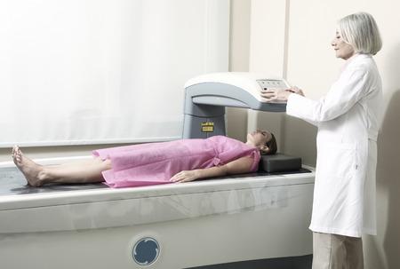 Examen del doctor de sexo femenino en la mujer de 40 años en Densitómetro del hueso de la máquina.