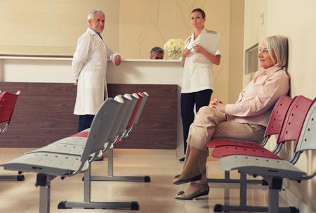 pacientes: Paciente mayor de la mujer sentada en la sala de espera del hospital con el personal médico en el mostrador. Foto de archivo