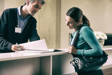 secretarias: Feliz paciente en 40 años se registren en el mostrador de recepción del hospital con el registro de datos de los empleados.