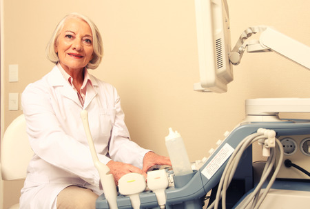 Happy mature female doctor using ultrasound scanner. Echography machine. photo