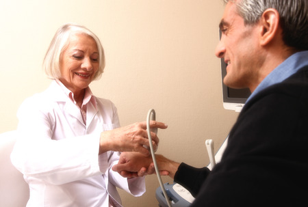 Mature female doctor scanning man in 40s. Wrist and arm exam. photo