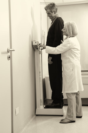 Man standing on weight machine with female doctor analyzing results. photo