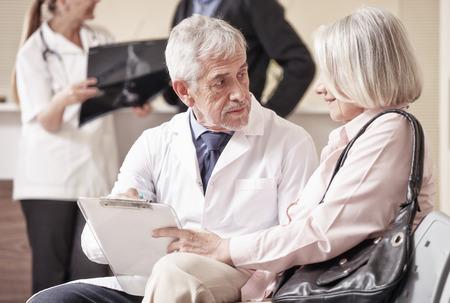 pacientes: Doctor de sexo masculino mayor que muestra los resultados médicos a su paciente mujer femenina con análisis de rayos x en segundo plano.