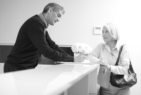 Senior female patient at hospital reception desk with man in 40s collecting personal data. Stock Photo