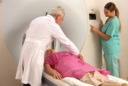 ct scan: Senior male doctor and female assistant examining woman in 70s with CT scanner. Stock Photo