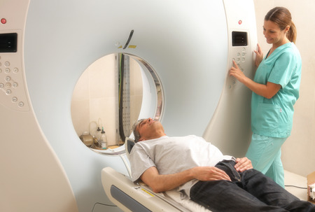 computerised: Young female doctor examining man in 40s with CT scanner. Computerised tomography.