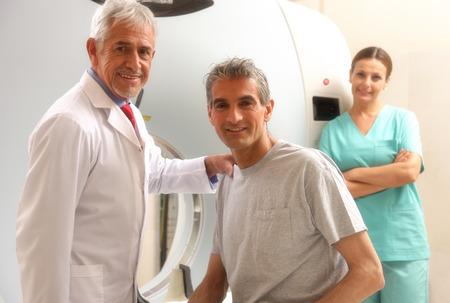 Gelukkig senior arts met zijn mannelijke patiënt bij CT-scanner machine. Vrouwelijke assistent op de achtergrond. Stockfoto