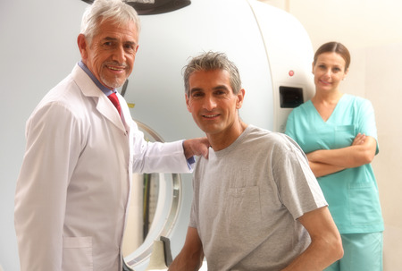 cancer patient: Happy senior doctor with his male patient at CT scanner machine. Female assistant on background.