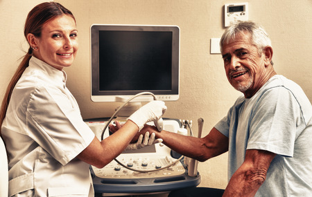Woman doctor examing patient man wrist with ultrasound. photo