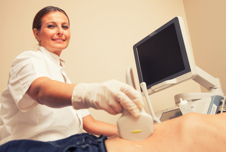 Happy woman doctor analyzing male patient with abdomen ultrasound. photo
