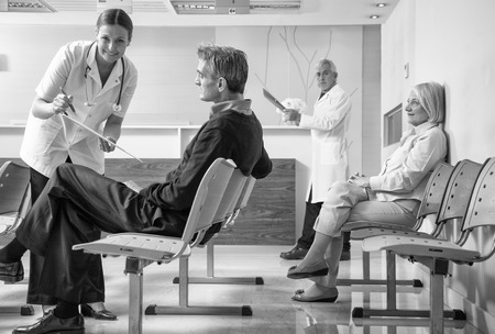 Doctors and patients in hospital waiting room. photo