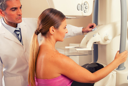 Male doctor checking mammography machine scan with patient woman in 40s. Stock Photo