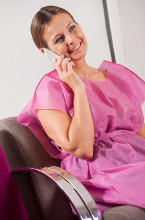Woman patient in 40s speaking at the mobile phone in hospital waiting room. photo