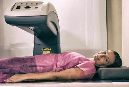 Woman in her 40s undergoing scan at bone densitometer machine. Stockfoto