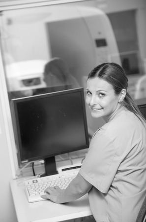 Young female doctor smiling working at monitor of mri machine scanner. photo