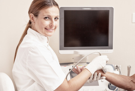 Woman doctor analyzing patient arm with tendon sonography.
