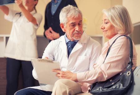 pacientes: Los médicos y los pacientes en la sala de espera del hospital. Médico de sexo masculino mayor que explica los exámenes médicos a la mujer paciente.