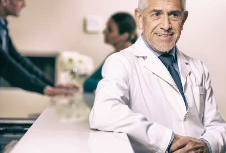 Smiling senior male doctor smiling at hospital reception desk, female patient speaking with young doctor on background. photo