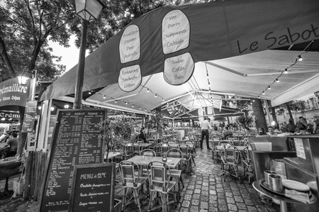 PARIS - JUNE 21, 2014: Tourists enjoy life in Montmartre narrow streets. Montmartre area is among most popular destinations in Paris, with its typical cafe and restaurants