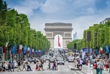 PARIS - JULY 20, 2014: Tourists on the famous Champs Elysees Avenue. With its cafes and luxury shops the Champs Elysees is one of the worlds most famous streets.