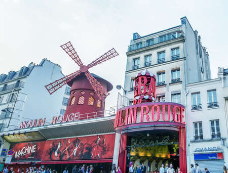 scandalous: PARIS, FRANCE - JULY 22: The Moulin Rouge during the day, on July 22, 2014 in Paris, France. Moulin Rouge is the most famous Parisian cabaret and it created the modern can-can dance Editorial