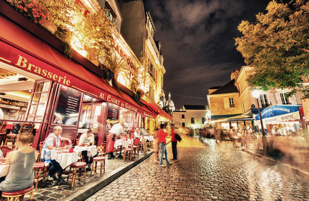 restaurant exterior: PARIS - JUNE 23, 2014: Tourists and locals walk in Montmartre streets at night. Montmartre attracted many famous modern painters in the early 20th century