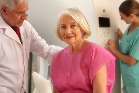computerised: Senior male doctor and female assistant examining woman in 70s with CT scanner. Computerised tomography.